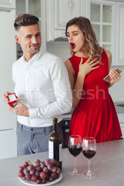 Portrait of a cheerful man proposing to his shocked girlfriend Stock photo © deandrobot