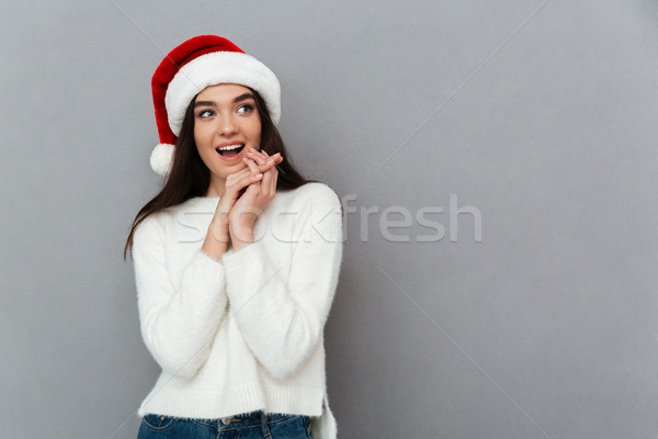 Portrait of a cheery lovely girl wearing red santa hat Stock photo © deandrobot