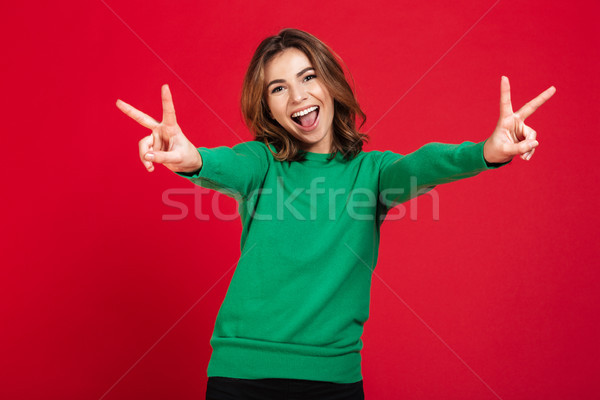 Happy young pretty woman showing peace gesture. Stock photo © deandrobot