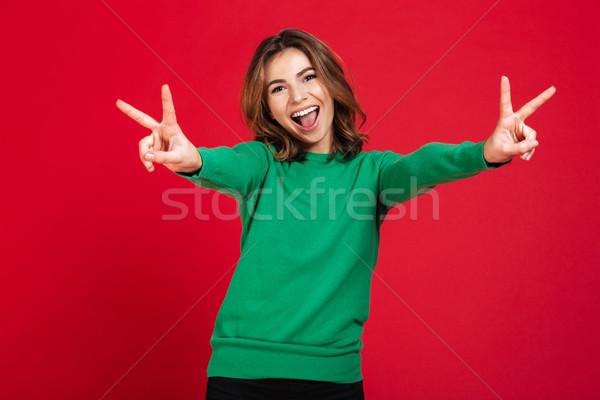 Feliz jovem mulher bonita paz gesto Foto stock © deandrobot