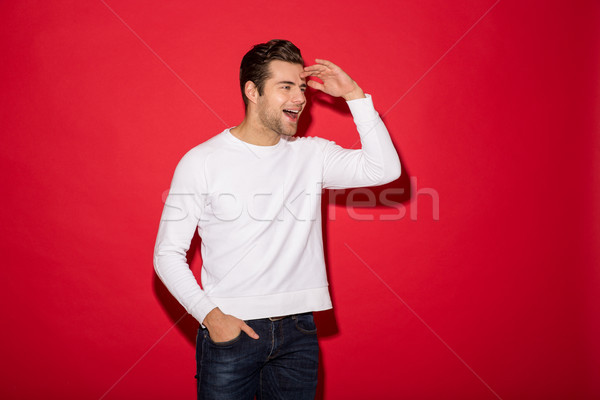 Happy man in sweater looking away with open mouth Stock photo © deandrobot