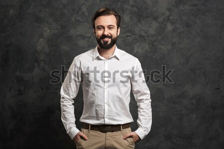 Portrait of young man in white shirt posing on camera with broad Stock photo © deandrobot