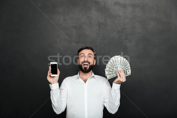 Portrait of ecstatic man expressing online earnings with holding Stock photo © deandrobot