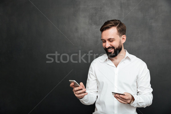 Portrait of cheerful man making online payment in internet using Stock photo © deandrobot