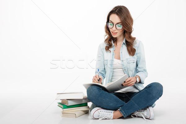 Geconcentreerde jonge vrouw student schrijven merkt afbeelding Stockfoto © deandrobot