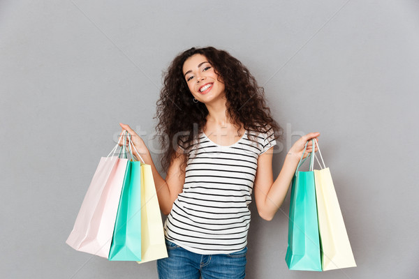 Picture of trendy fashion woman posing on camera with lots of pa Stock photo © deandrobot