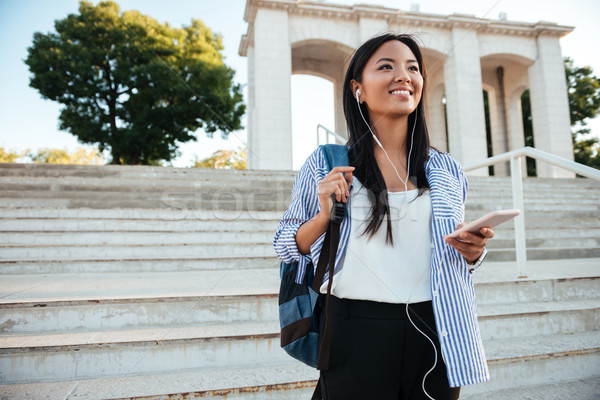 Happy young asian woman in striped shirt and earphones, listenin Stock photo © deandrobot