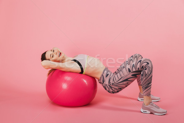 Side view of Happy sportswoman doing exercise with fitness ball Stock photo © deandrobot