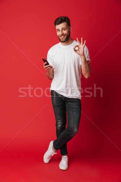 Happy young man showing okay gesture. Stock photo © deandrobot