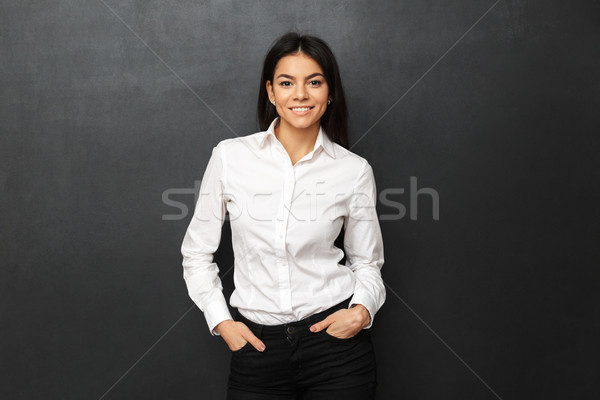 Image of businesslike woman wearing formal outfit smiling at cam Stock photo © deandrobot