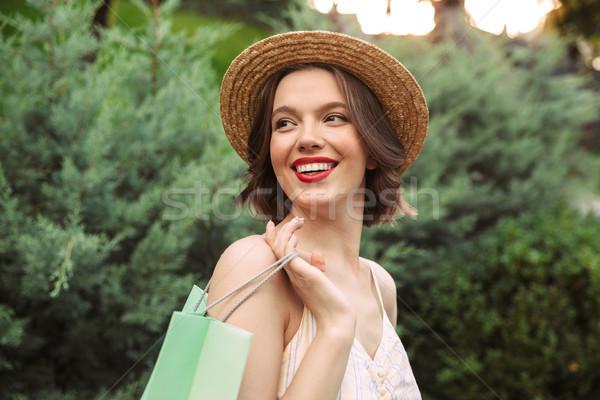 улыбающаяся женщина платье соломенной шляпе позируют пакеты Сток-фото © deandrobot