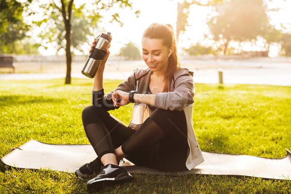Fotó elégedett fitnessz nő 20-as évek sportruha ivóvíz Stock fotó © deandrobot