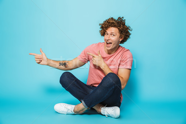 Portrait of a happy young curly haired man pointing away Stock photo © deandrobot