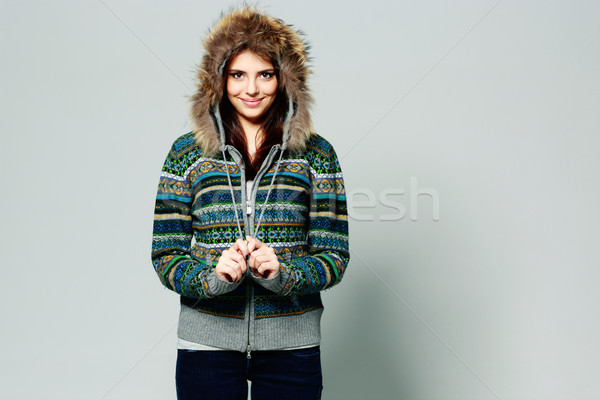 Young happy smiling woman in warm winter outfit on gray background Stock photo © deandrobot