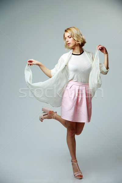 Young woman in light suit dancing with air Stock photo © deandrobot
