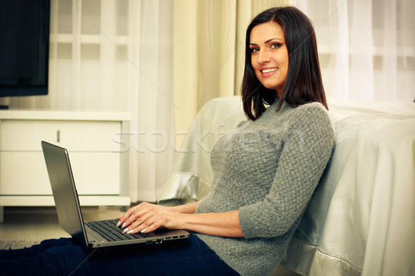 Middle-aged cheerful woman sitting on the floor with laptop at home Stock photo © deandrobot