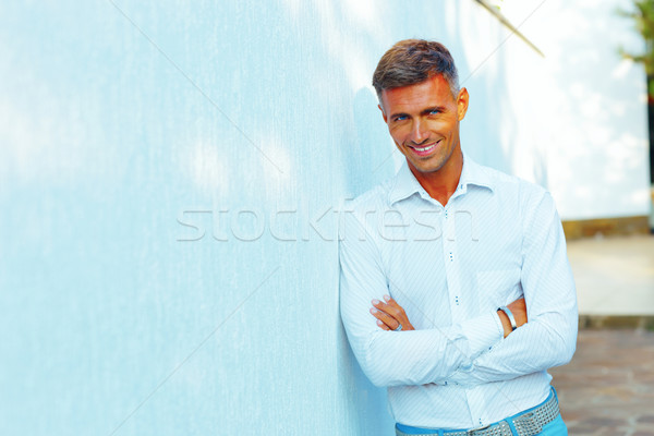 Handsome man standing outdoors with arms folded Stock photo © deandrobot