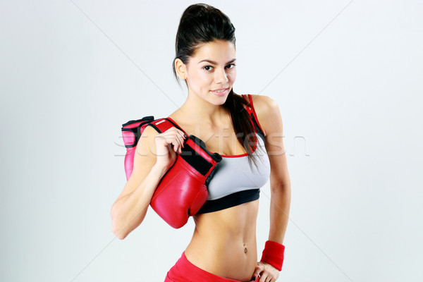 Young smiling fitness woman standing with boxing gloves on gray background Stock photo © deandrobot