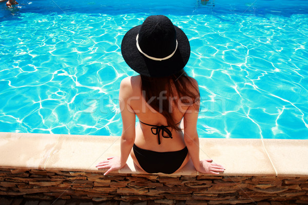 Back view portrait of a young woman sitting on the ledge of the pool Stock photo © deandrobot
