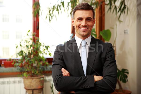 Sonriendo empresario pie armas doblado oficina Foto stock © deandrobot
