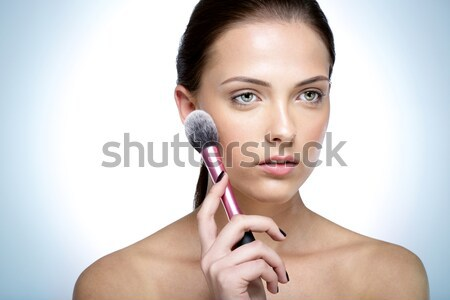 Portrait of a young beautful woman holding cosmetic brush  Stock photo © deandrobot