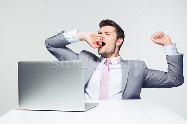 Businessman sitting at the table and yawning Stock photo © deandrobot