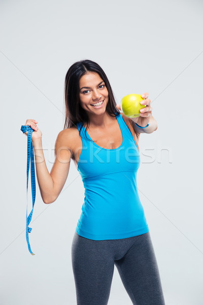 Sporty woman holding apple and measuring tape Stock photo © deandrobot