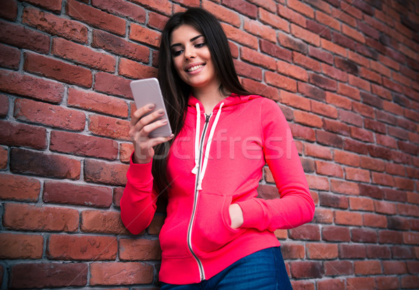 Smiling woman using smartphone Stock photo © deandrobot