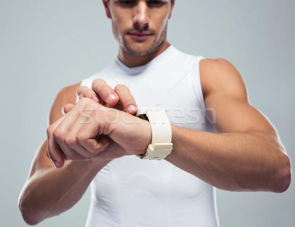 Fitness man using smartwatch Stock photo © deandrobot