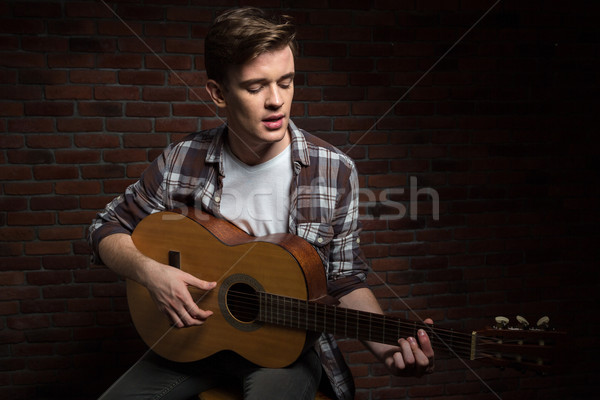 Handsome concentrated young man playing acoustic guitar and singing Stock photo © deandrobot