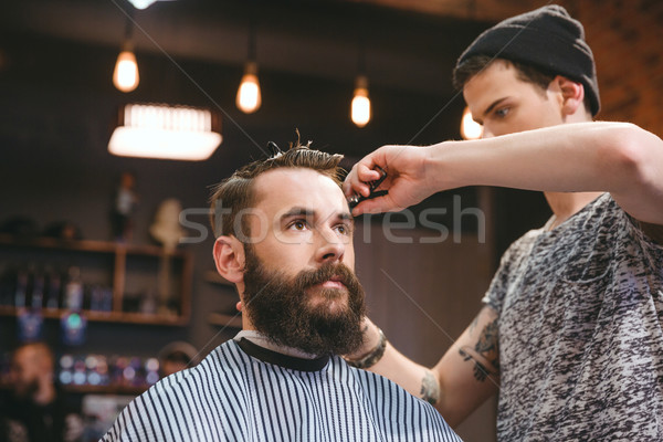 Skillful barber cutting hair of young man with beard  Stock photo © deandrobot