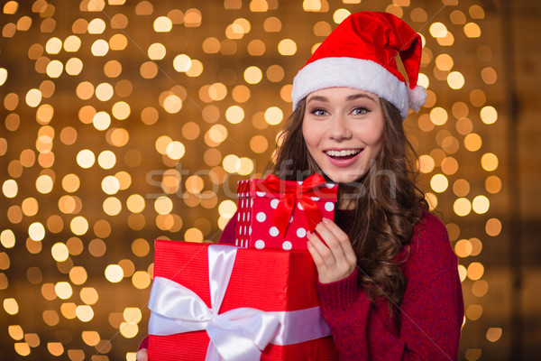 Portrait of positive attractive girl in santa hat with presents  Stock photo © deandrobot