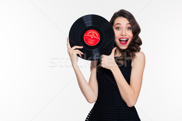 Beautiful positive woman holding vinyl record and showing thumbs up  Stock photo © deandrobot