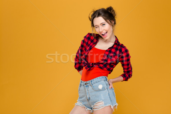 Playful happy young woman standing and winking  Stock photo © deandrobot