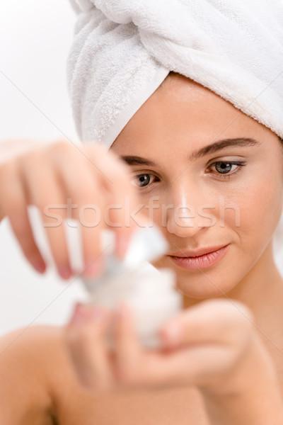 Closeup of beautiful natural young woman opening face cream  Stock photo © deandrobot