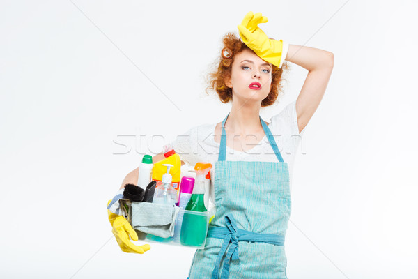 Tired woman in yellow gloves holding box with detergents  Stock photo © deandrobot