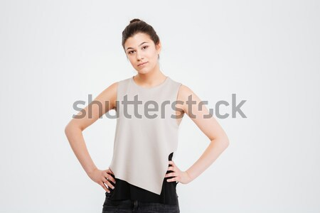 Confident serious young business woman standing with hands on waist Stock photo © deandrobot