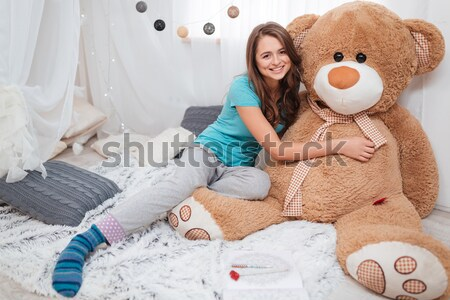 Cute girl with big plush bear sitting in children room  Stock photo © deandrobot