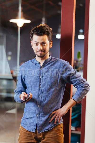 Man holding smartphone in office Stock photo © deandrobot