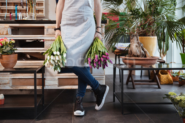 Woman florist in apron and sneakers with two tulips bouquets Stock photo © deandrobot