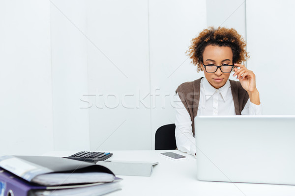 Concentrated african american woman accountant working in office using laptop Stock photo © deandrobot