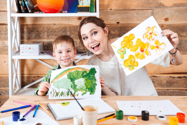 Happy cute little boy and his mother showing their paints  Stock photo © deandrobot