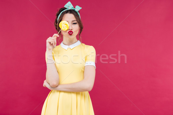 Funny lovely pinup girl covered one eye with yellow lollipop Stock photo © deandrobot
