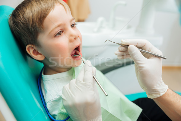 Boy sitting with mouth opened during oral checkup at dentist Stock photo © deandrobot