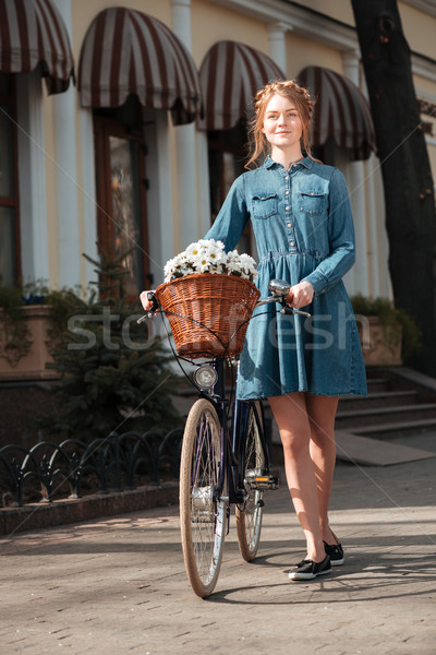 Smiling woman with bicycle walking outdoors Stock photo © deandrobot