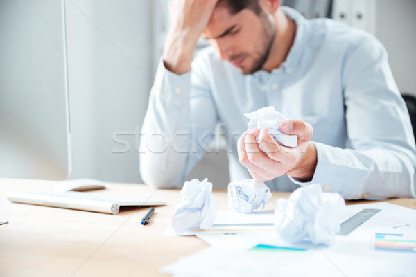 Tired desperate young businessman working and crumpling paper Stock photo © deandrobot