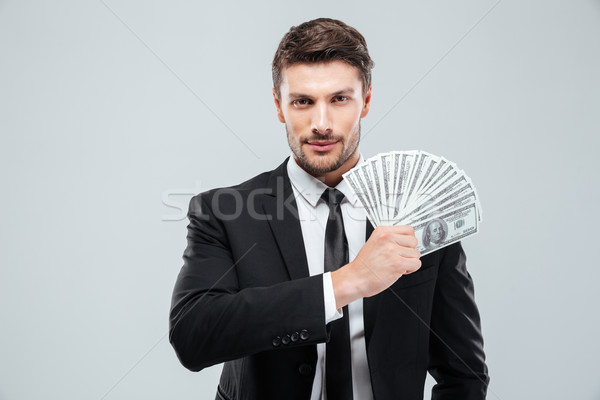Portrait of handsome young businessman holding money Stock photo © deandrobot