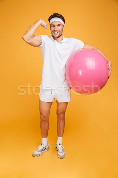 Young handsome sportsman holding fitness ball and showing biceps Stock photo © deandrobot