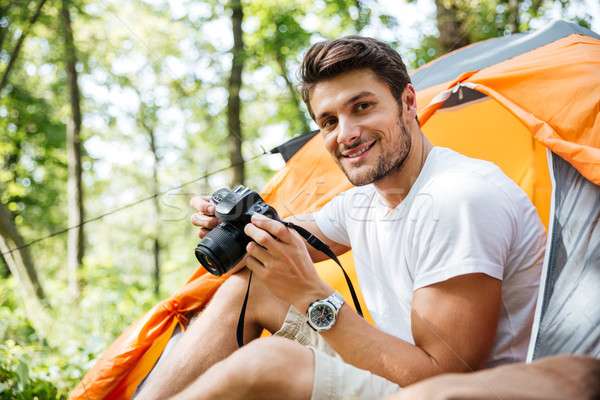 Man tourist sitting and using photo camera in touristic tent Stock photo © deandrobot
