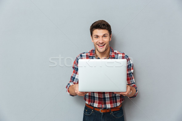 Cheerful young man in checkered shirt standing and holding laptop Stock photo © deandrobot